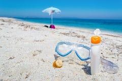 Suncream en het duiken masker op het zand stock foto