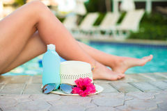 Suncream, hat, sunglasses, flower and tanned female legs near pool Stock Photography