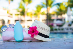 Suncream, hat, sunglasses, flower and tower near swimming pool Stock Photo