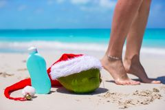 Suncream, Santa Hat on coconut and tanned female legs at white beach Royalty Free Stock Photography