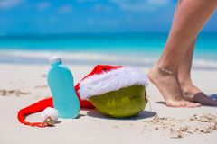 Suncream, Santa Hat on coconut and tanned female Stock Images