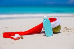Suncream and Santa Hat on coconut at white exotic Royalty Free Stock Photo