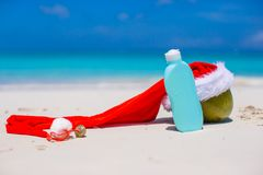 Suncream and Santa Hat on coconut at white exotic Stock Photos