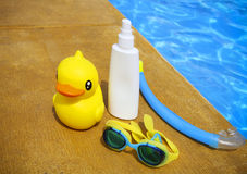 Suncream, snorkel, goggles and yellow rubber duck Stock Photos