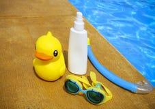Suncream, snorkelt, beschermende brillen en gele rubbereend Stock Foto's
