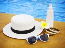 Suncream solglasögon, hatt, armband nära simbassängen royaltyfria foton