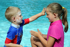 Suncreen protection. Children applying sunscreen on each other's faces Stock Photos