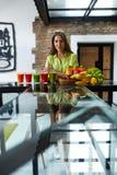 Sund äta härlig kvinna med nya Juice Smoothie Indoors Arkivbilder
