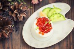 Sund aptitretare: sandwichwithägg som är välfyllt med den röda kaviaren och gurkan spelrum med lampa Top beskådar Arkivfoto