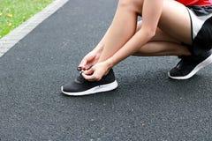 Sund asiatisk kvinna som binder skosn?re p? rinnande skor p? gatan Kondition- och genomk?rareWellnessbegrepp arkivbild