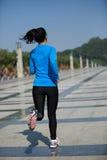 Sund asiatisk kvinna som joggar på staden Arkivbild