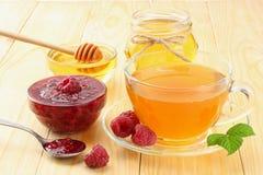 Sund bakgrund hallon med hallondriftstopp, honung och te på ljus träbakgrund Royaltyfri Bild