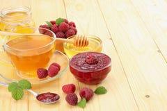 Sund bakgrund hallon med hallondriftstopp, honung och te på ljus träbakgrund Royaltyfria Foton