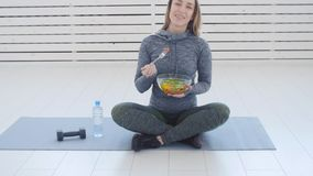 sund begreppsmat Lycklig kvinna som äter sund grön sallad efter genomkörare i en vit inre stock video