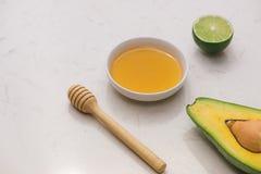 sund begreppsmat Ny organisk avokado med honung på tabellen Arkivbild