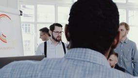 Sund bekväm arbetsplats Ledande lag för lycklig ung vdaffärsman på det moderna kontoret som möter RÖD EPOS för ultrarapid stock video