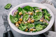 Sund bunke för grön sallad med spenat, quinoaen, kikärtar och röda lökar arkivbilder