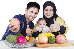 Sund familj med frukter och tummar-upp royaltyfria foton