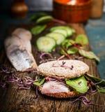 Sund fisksmörgås med sillen, gurkan och groddar på det lantliga köksbordet Royaltyfria Bilder
