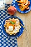 Sund frukost: Belgiska dillandear med persikaskivor och kräm dekorerade mintkaramellsidor och den blåa servetten Royaltyfri Bild
