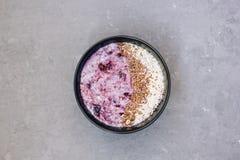 Sund frukost för morgon med blåbärdriftstopp - vetehavregröt med bär och linfrö på konkret bakgrund lantligt arkivfoton