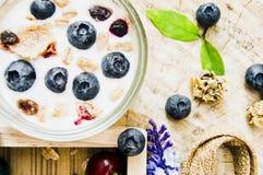 Sund frukost f?r b?sta sikt med ny yoghurt, granola och mysli med k?rsb?ret och b?r i litet exponeringsglas p? tr?magasinet, mat arkivbilder