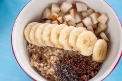 Sund frukost, havremjöl, banan, päron, honung, linfrö, chiafrö Arkivbild