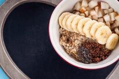 Sund frukost, havremjöl, banan, päron, honung, linfrö, chiafrö royaltyfri fotografi