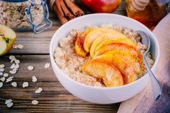 Sund frukost: havremjölbunke med caramelized äpplen, kanel och honung Arkivfoto