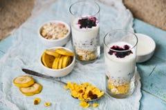 Sund frukost: hemlagad granola, banan, nya bär, yoghurt i exponeringsglaskoppar på ljus textilbakgrund Begreppet av healt Arkivbilder