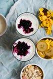 Sund frukost: hemlagad granola, banan, nya bär, yoghurt i exponeringsglaskoppar på ljus textilbakgrund Begreppet av healt Royaltyfri Bild