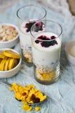 Sund frukost: hemlagad granola, banan, nya bär, yoghurt i exponeringsglaskoppar på ljus textilbakgrund Begreppet av healt Royaltyfria Bilder