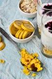 Sund frukost: hemlagad granola, banan, nya bär, yoghurt i exponeringsglaskoppar på ljus textilbakgrund Begreppet av healt Royaltyfri Foto