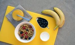 Sund frukost med granola, grekisk för bär, knäpp och ny orange fruktsaft för yoghurt, på gul skärbräda på grå bordduk royaltyfri foto