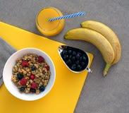 Sund frukost med granola, grekisk för bär, knäpp och ny orange fruktsaft för yoghurt, på gul skärbräda på grå bordduk royaltyfri fotografi
