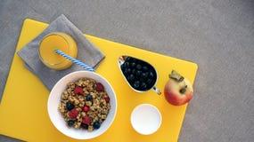 Sund frukost med granola, grekisk yoghurt, äpplet, bär och ny orange fruktsaft på gul skärbräda på grå bordduk royaltyfria bilder