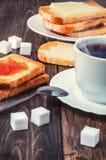 Sund frukost med kopp te, bröd, smör och driftstopp arkivfoto