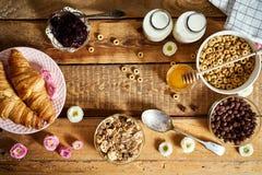 Sund frukost med olika typer av frukostsädesslag med honungmarmeladgiffel och att mjölka arkivfoto