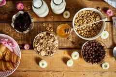 Sund frukost med olika typer av frukostsädesslag med honungmarmeladgiffel och att mjölka royaltyfria bilder