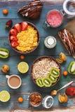 Sund frukost med sädesslag, frukter, bär, kaffe på en blå lantlig träbakgrund Sikten uppifrån, framlänges lekmanna- royaltyfri foto