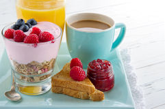 Sund frukost med yoghurt, bär, fruktsaft, rostat bröd och kaffe arkivfoto