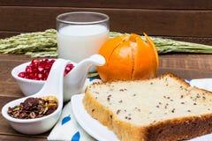 Sund frukost: mjölka, bära frukt, chokladgranola och bröd för helt vete Arkivbilder