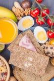 Sund frukost: mysli med bär, ägg, tomater, bröd Arkivbilder
