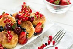 Sund frukost: ostpannkakor med gräddfil och nya mogna bär Royaltyfria Bilder