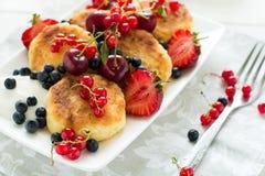 Sund frukost: ostpannkakor med gräddfil och nya mogna bär Fotografering för Bildbyråer