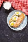 Sund frukost - rostat bröd med avokadot, ägget och exponeringsglas av mjölkar Royaltyfria Foton