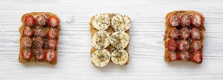 Sund frukost som bantar begrepp Strikt vegetarianrostade bröd med jordnötsmör, frukter och chiafrö över vit träyttersida, tävlar  royaltyfri fotografi
