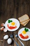 Sund frukost: stekt ägg på trätabellen och tre skivor av bröd med gräsplaner, ägg, tomater och peppar Arkivfoton
