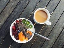 Sund frukost: yoghurt plommoner, kiwibär, aprikors, chiafrö, kaffe Arkivfoto