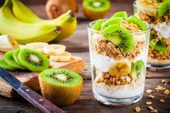 Sund frukost: yoghurtparfait med granola, bananen och kiwin Arkivfoton